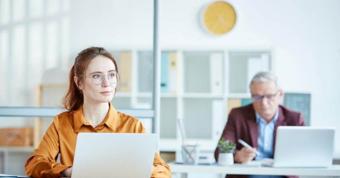 Young secretary sitting at the table and using laptop with manager working in the background at office