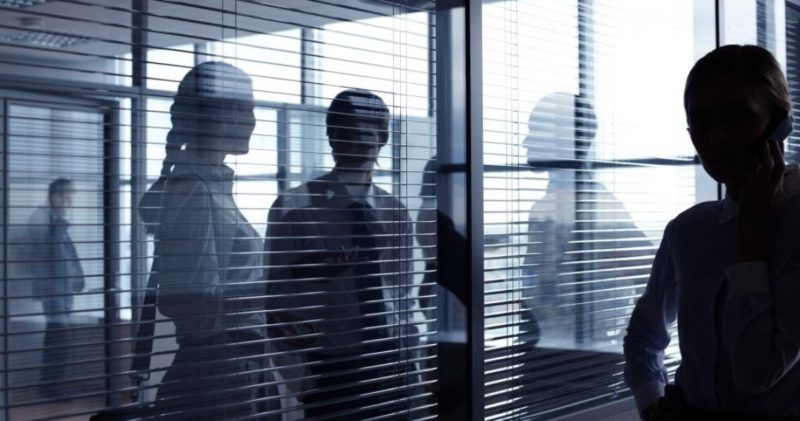 Unrecognizable business people communicating behind glass wall with blinds